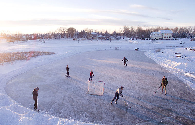 People playing pond hockey on a snowy winter day