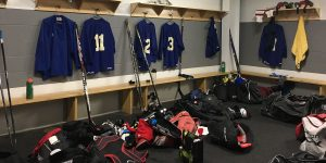A hockey dressing room filled with hockey equipment.