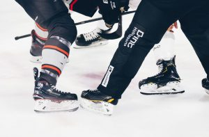 Players with various skates taking a faceoff is the cover photo for our Skate Fitting Guide.