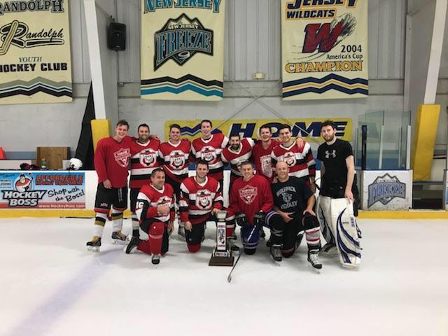 A men's league team in matching hockey jerseys taking a team photo