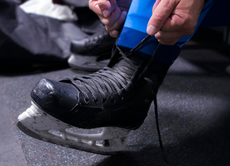 Hands getting a skate ready in a dressing room, and showing that boot punch can be on any skate.
