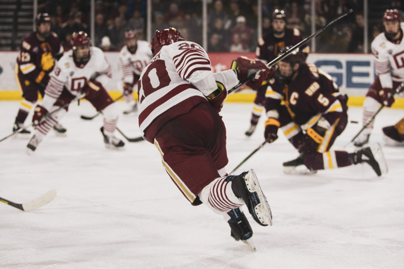 A NCAA hockey player taking a shot on goal.