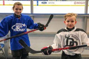 Two kids holding Diezel Hockey sticks