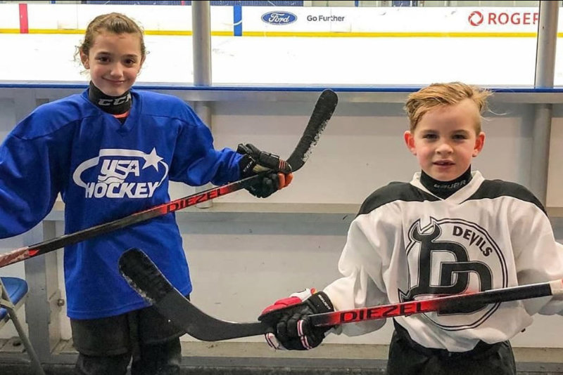 Two kids holding Diezel Hockey sticks